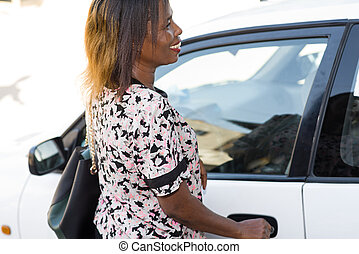 Happy young woman opening the car