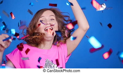 Happy young woman or teen girl with sequins and confetti at party