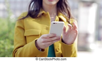 technology, lifestyle and people concept - smiling young woman or teenage girl with smartphone texting on city street