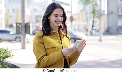 happy young woman or teenage girl with smartphone