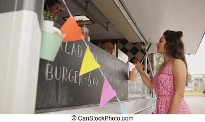 happy young woman ordering meal at food truck - street sale,...