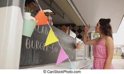 happy young woman ordering wok at food truck - street sale,...