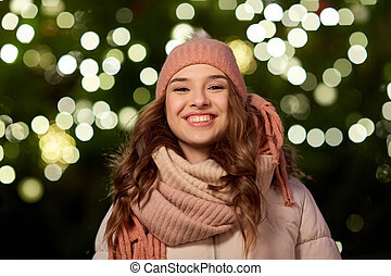 happy young woman over christmas tree lights - holidays and...