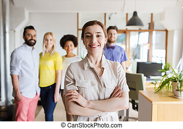 happy young woman over creative team in office - business,...