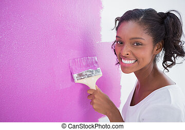 Happy young woman painting her wall