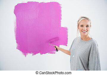Happy young woman painting her wall pink