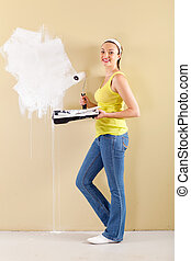 happy young woman painting the wall
