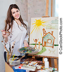 Happy young woman paints on canvas with oil paints