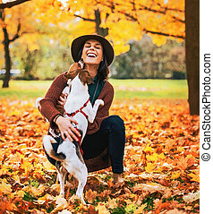Happy young woman playing with dog outdoors in autumn