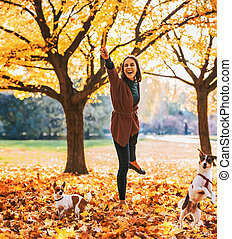 Happy young woman playing with dogs outdoors in autumn