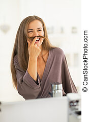 Happy young woman playing with hair