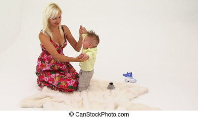 Happy Young Woman Playing With Her Small Baby Boy Sitting On The Floor