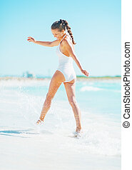 Happy young woman playing with waves on beach