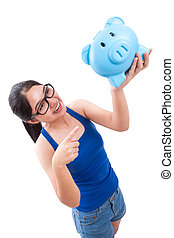 woman pointing at piggy bank