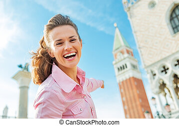 Happy young woman pointing on campanile di san marco in venice,