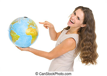Happy young woman pointing on globe