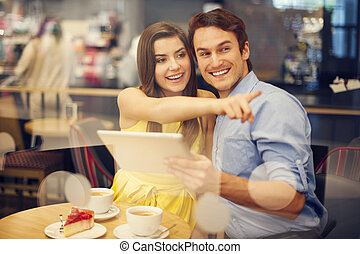 Happy young woman pointing something while sitting in cafe