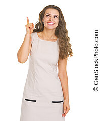 Happy young woman pointing up on copy space