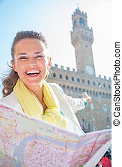 Happy young woman pointing with map pointing on palazzo vecchio