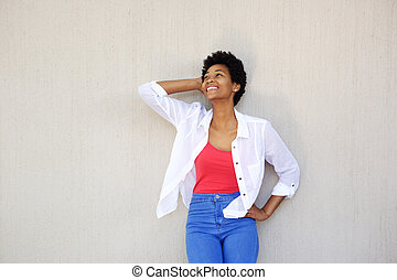 Happy young woman posing against a wall