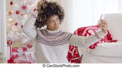 Happy young woman posing for a Christmas selfie