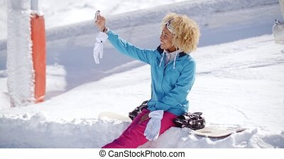 Happy young woman posing for a winter selfie