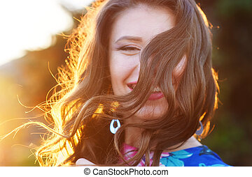 happy young woman posing in the Park against sunset
