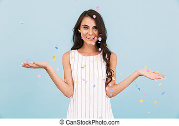Happy young woman posing isolated over blue background wall...