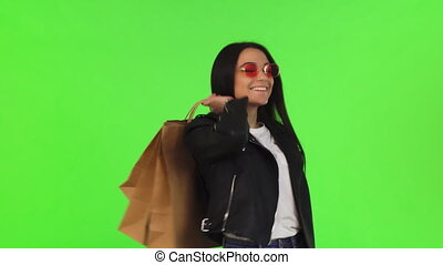 Happy young woman posing with her shopping bags on chromakey