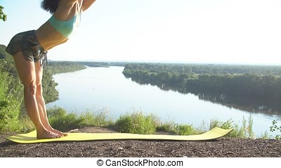 Happy young woman practicing yoga at sunset. Healthy active lifestyle concept.