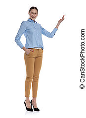 happy young woman presenting to side on white background