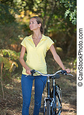 happy young woman pushing bicycle in the forest