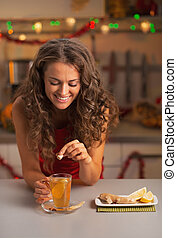Happy young woman putting brown sugar cube into ginger tea