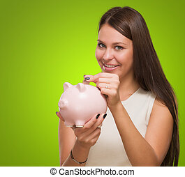 Happy Young Woman Putting Coin In Piggy bank