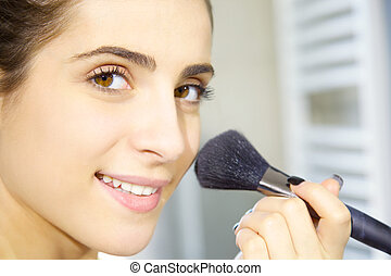 Happy young woman putting makeup in the morning in bathroom closeup