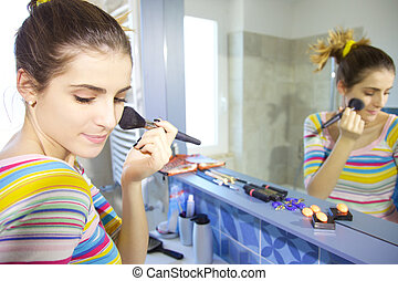 Happy young woman putting makeup in the morning in bathroom