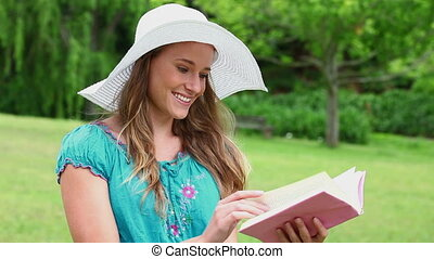 Happy young woman reading a fascinating book