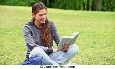 Happy young woman reading a fascinating novel in a park