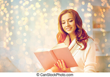 happy young woman reading book at home