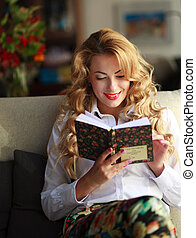 Happy young woman reading book on couch at home