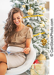 Happy young woman reading magazine near christmas tree