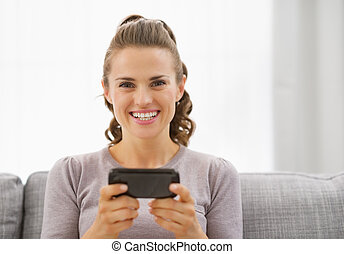 Happy young woman reading sms