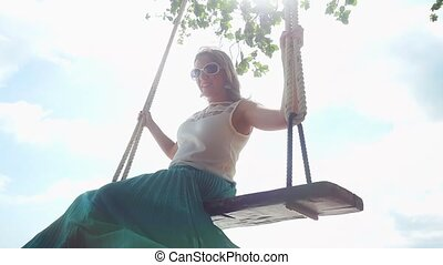 Happy young woman relaxes on the swing at the stones beach in slow motion with beautiful sun flare effect.