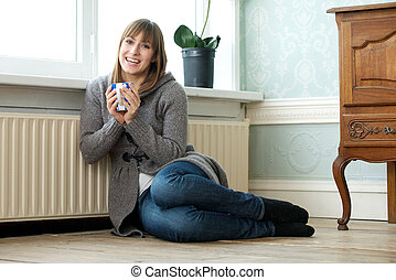 Happy young woman relaxing at home with a cup of tea