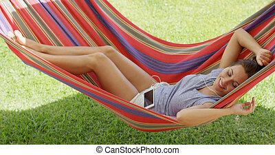 Happy young woman relaxing in a colorful hammock