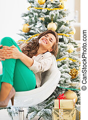 Happy young woman relaxing near christmas tree