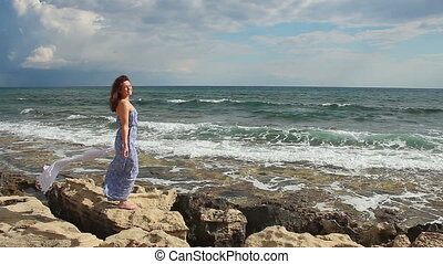 """Happy young woman relaxing on rocky beach in windy weather, looking at camera"""