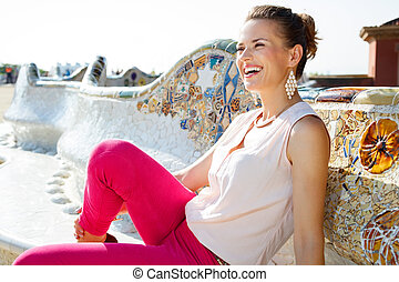 Happy young woman relaxing on the famous trencadis style bench