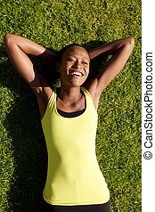 Happy young woman resting on grass after workout