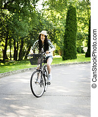 Happy young woman riding a bicycle in the park